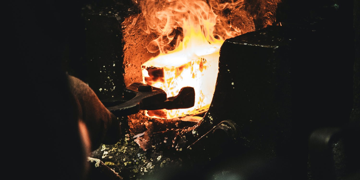 Heavy metal tongs pulling a block of molten steel out of a forge.