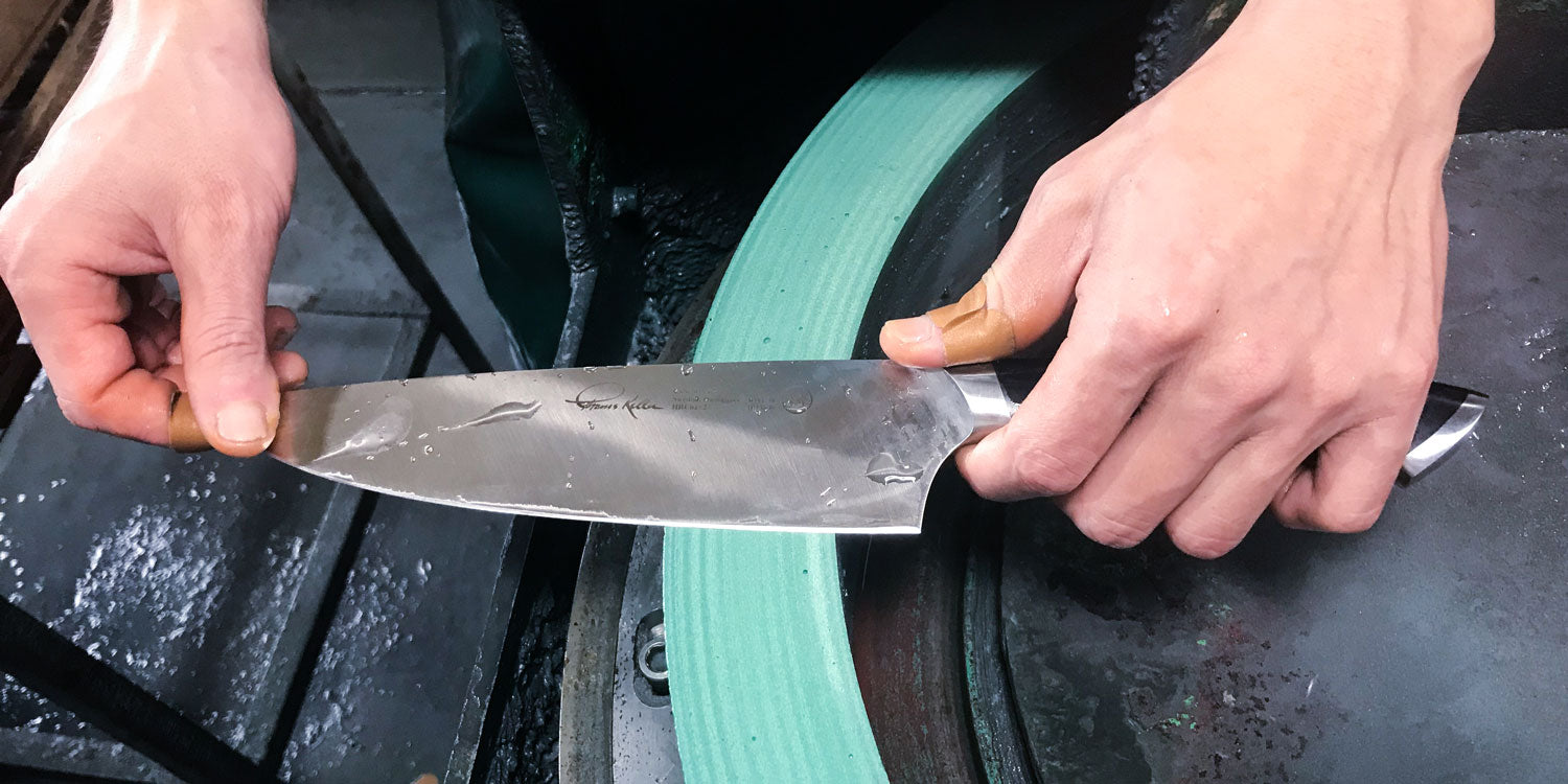 A close up of a bladesmiths hands as the hand sharpen a knife on a green sharpening wheel.