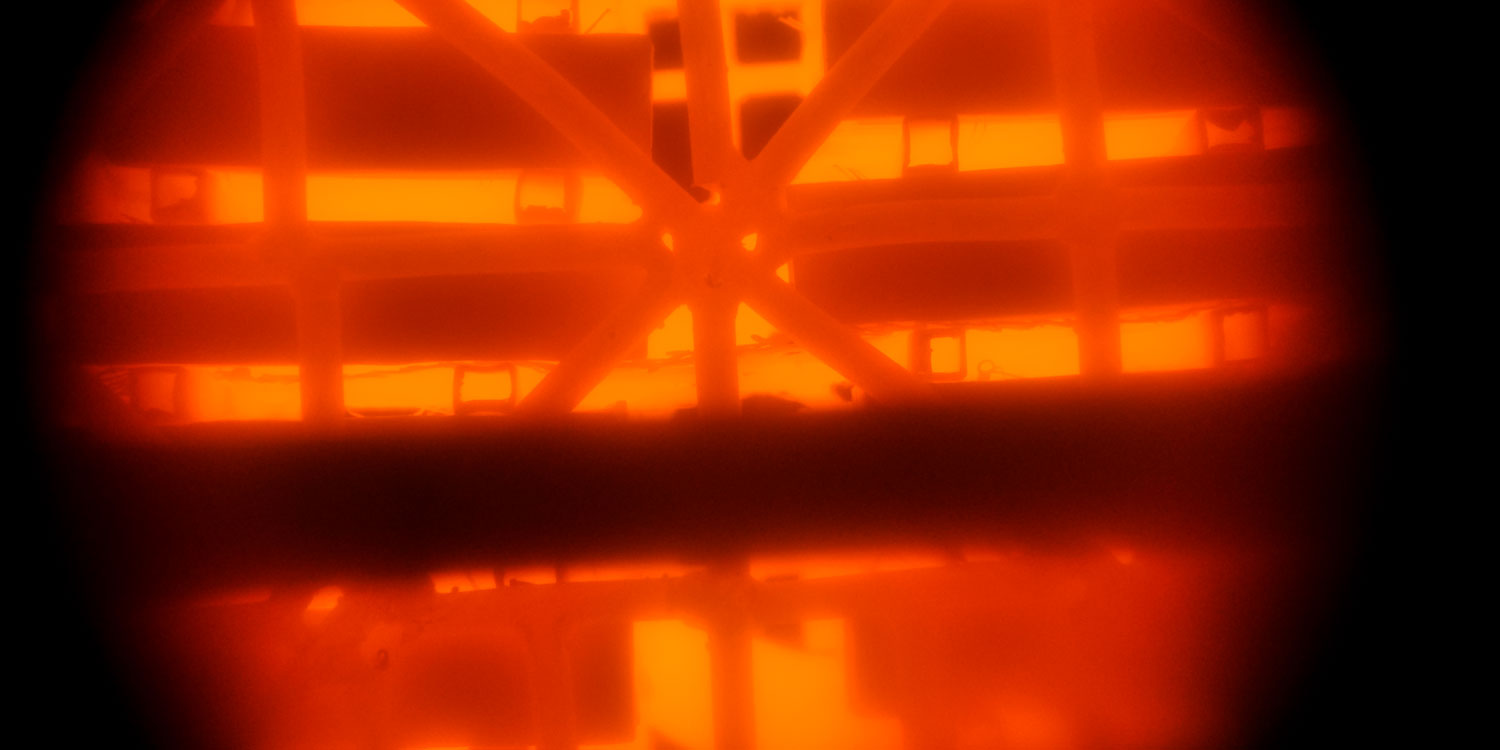 A view into the inside of a forge that is glowing bright orange red.