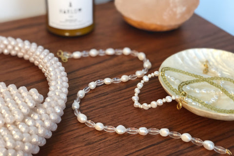 Beaded Bag and freshwater pearl and glass beaded necklaces on a teak table