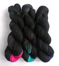 Load image into Gallery viewer, Black Like My Heart on a Superwash Merino/Nylon/Sparkle sock yarn.