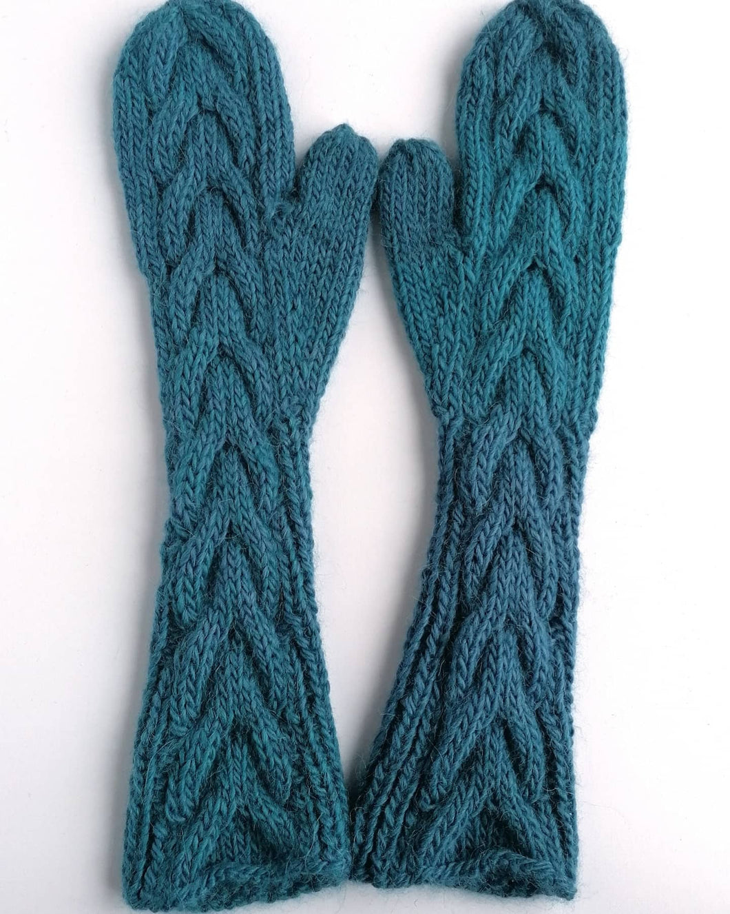 Hand knitted cabled mittens.
