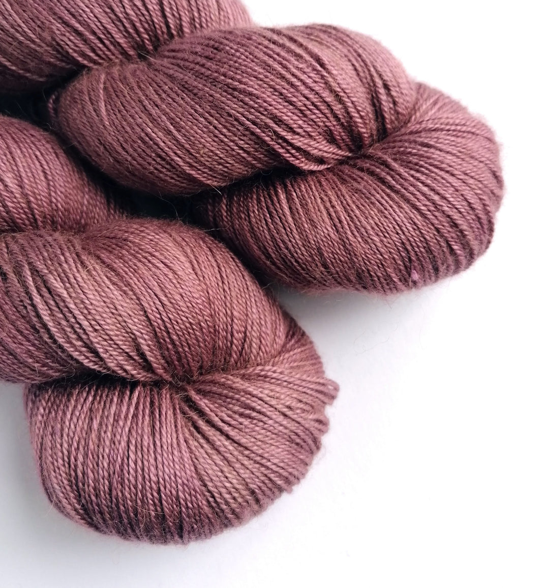 Hand dyed baby camel/silk 4ply/fingering weight yarn, in a dusky pink-brown semi-solid.