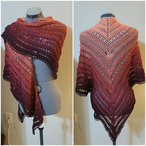 A triangular shawl with loose, open weave. The top is pale orange and fades into dark, almost black red.
