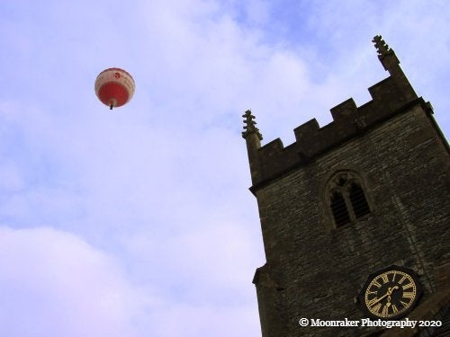 Photograph of a hot air balloon depicted in the air beside the top of a parish.