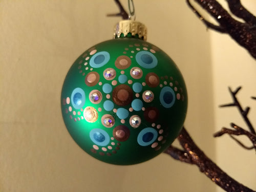 A painted swirl design on a green ornament. Embellished with crystal.