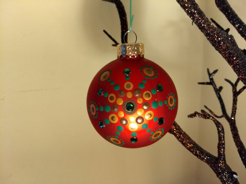 A painted starburst design in gold and green on a red ornament. Embellished with crystals.