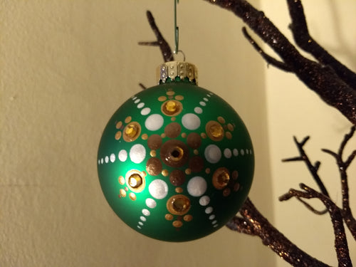 A painted starburst design in gold and white on a green ornament. Embellished with crystal.