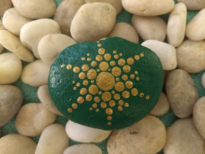 A small stone with a gold snowflake design on a green background.