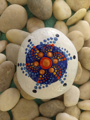 A small palm-sized meditation stone with a painted circular design in blue and orange.
