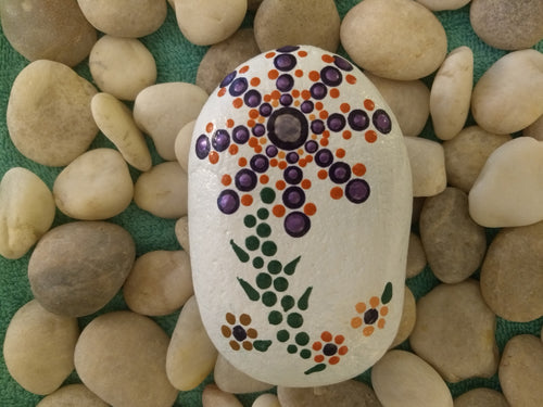 A hand-sized stone with a painted flower on a white background.