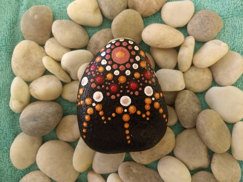 A hand-sized stone with a painted starburst pattern in red and orange.