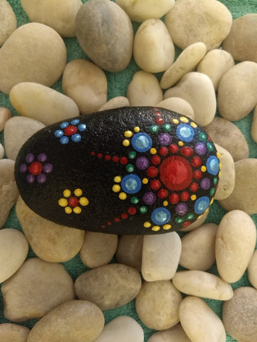 A palm-sized stone with a painted rainbow starburst design on a black background.