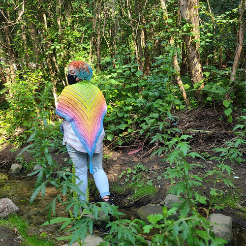 The creator of The Goblinarium stands in a forest wearing a triangular rainbow shawl.