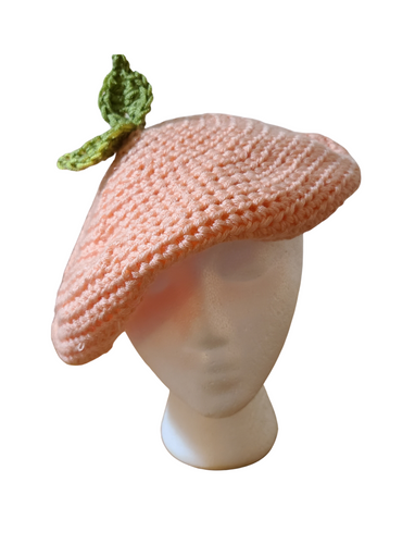 Crocheted yarn hat. Peach colored yarn. Green crocheted leaf on top