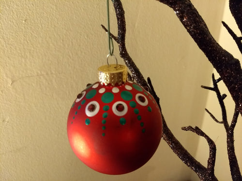A green and white design on a red ornament. Embellished with crystal.
