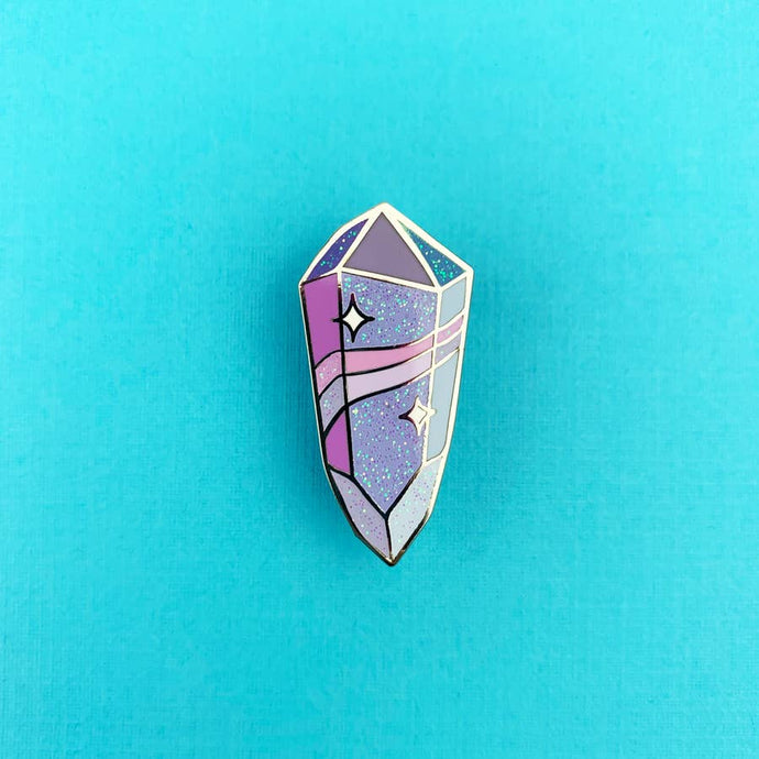 Enamel pin depicting a sparkling, stylized purple crystal.