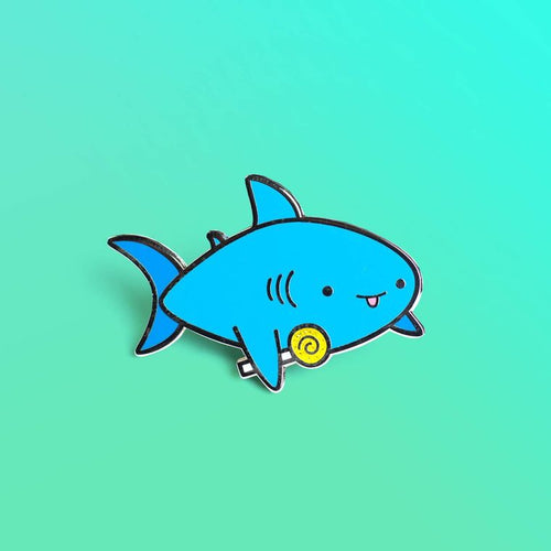 Enamel pin depicting a shark sticking its tongue out with a lollipop in its fin.
