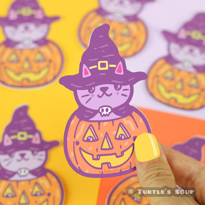 a cute lavender cat has its head poking out of a carved jack-o-lantern, the cat is wearing a black cape with a skull clasp and a black witch hat with a yellow buckle