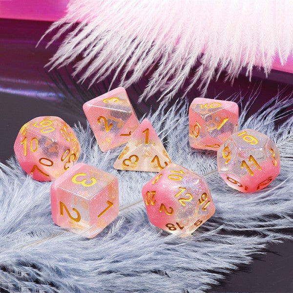 A tabletop dice set in translucent pink with gold numbers.