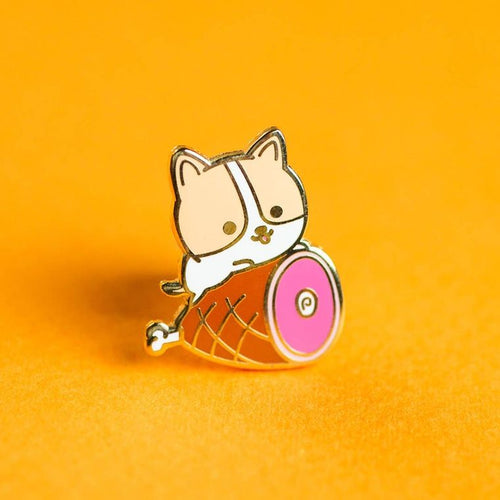 Enamel pin depicting a a happy corgi resting on ham.