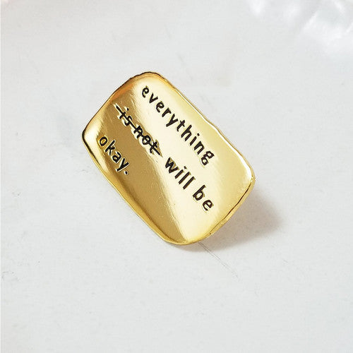 Enamel pin depicting the words