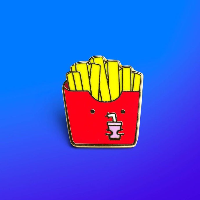 Enamel pin depicting a container of french fries with a cartoonish face, sipping from a drink with a straw.