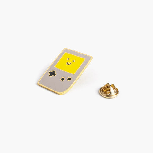 Enamel pin depicting an old-school Gameboy with a smiling screen.
