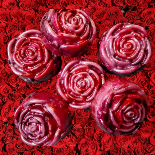 Red and pink rose-shaped soap on a background of red roses