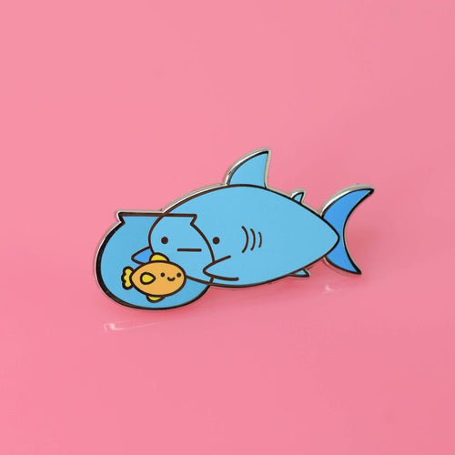 Enamel pin depicting a shark holding a fishbowl, watching a smiling goldfish.