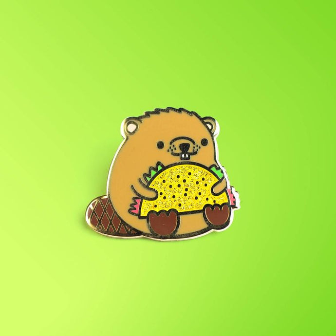 Enamel pin depicting a stylized beaver holding a taco in its arms.