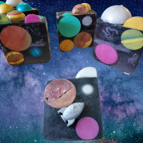 Square, glittery black soaps with colorful planets embedded. One of the soaps has a small silver spaceship adhered to the front.