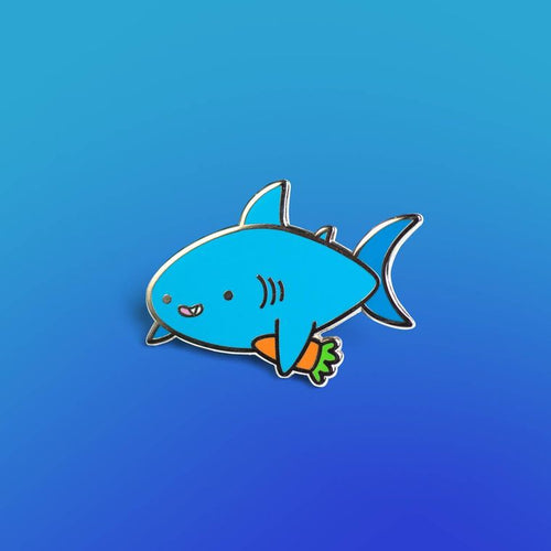 Enamel pin depicting a shark smiling a gap-toothed grin, with a carrot clutched in one fin.