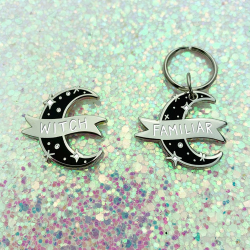 Enamel pin with a matching pet collar charm depicting a crescent moon in black with silver sparkles and a silver banner. The pin says