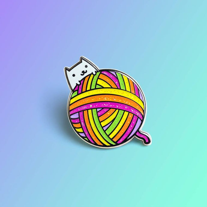 Enamel pin depicting a smiling white cat with a giant ball of colorful yarn.