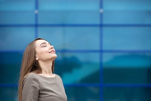 business woman breathing deeply with closed eyes