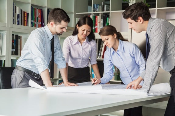 productive coworkers working in standing desk with pencil