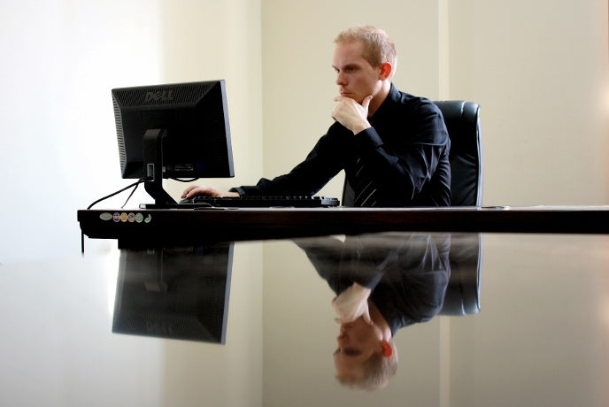 man working in his computer and reflecting in his desk