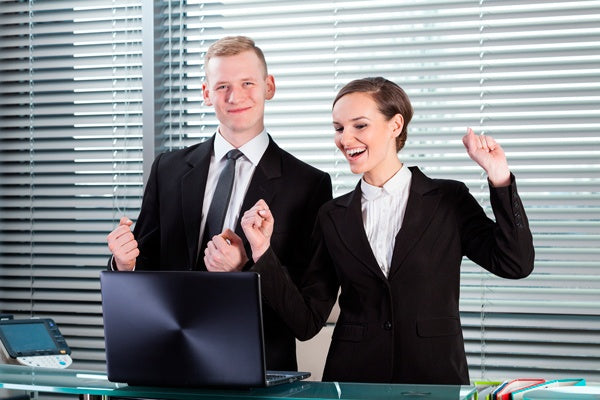 Coworkers in suits working while standing up