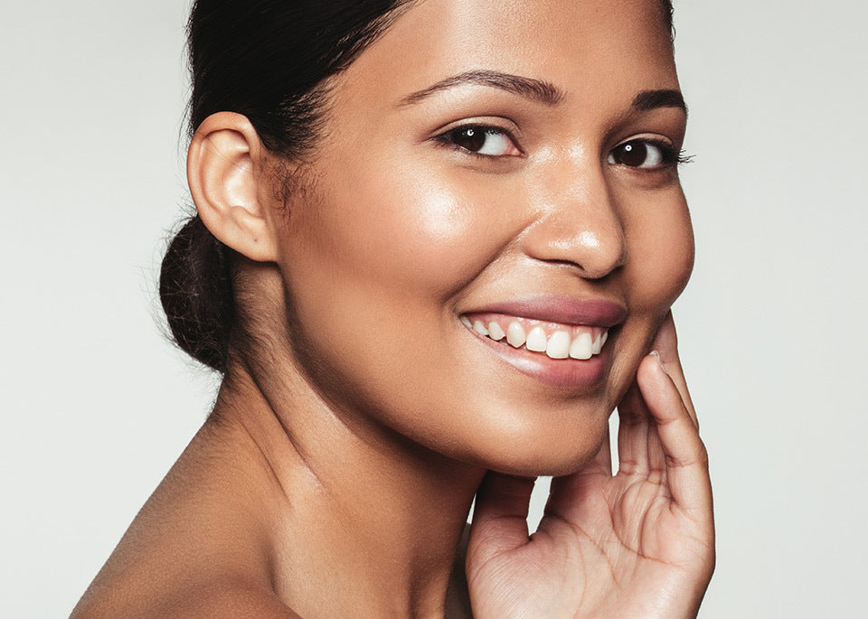 a smiling woman touching her soft face