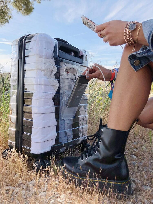 Image of a see through luggage that shows the protable battery being put into the luggage battery compartment.