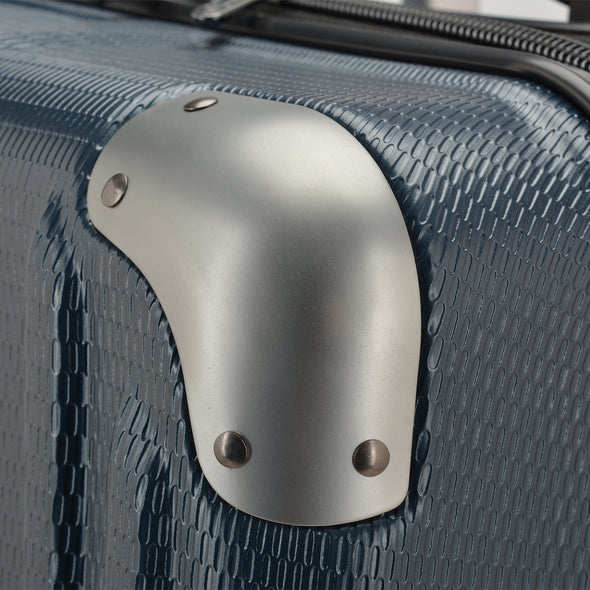 An image of the silver corner guard on the blue luggage.