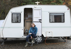 Katie and Baxter outside their caravan