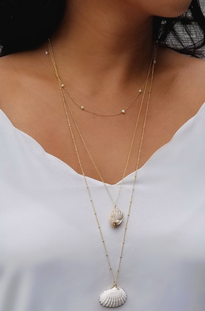 model wearing layered gold conch and clam shell necklaces and a pearl necklace