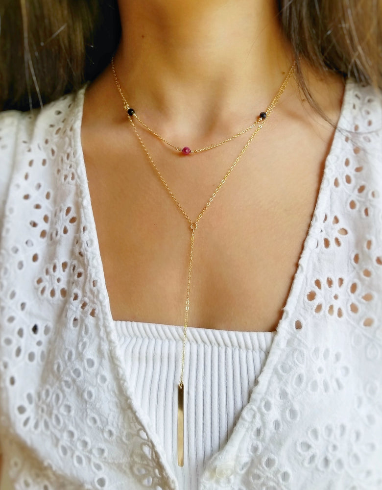 model wearing three stoned birthstone necklace layered with the gold drop bar necklace