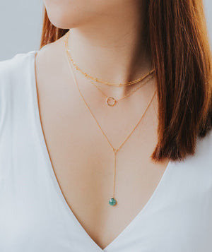 model wearing the emerald teardrop lariat necklace layered with the karma necklace and the milestone strand
