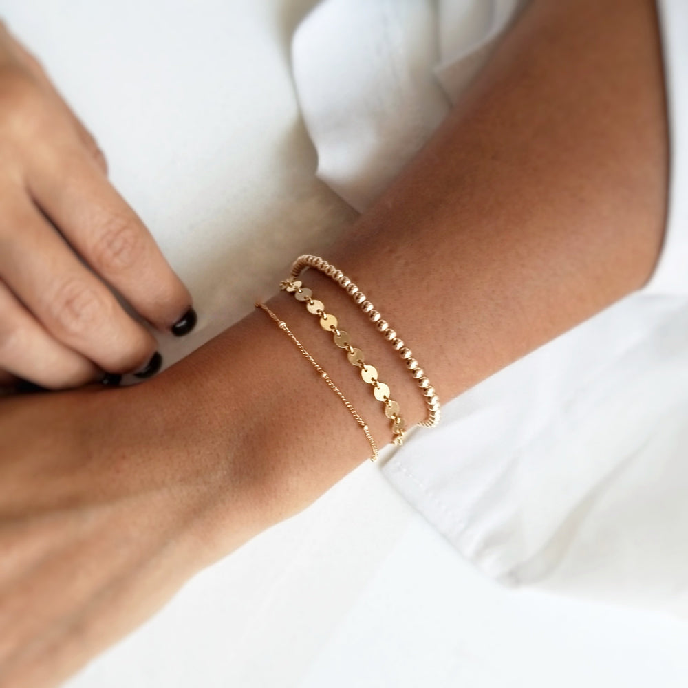 gold bracelet stack featuring the gold beaded bracelet layered with the gold coined and the gold satellite bracelet