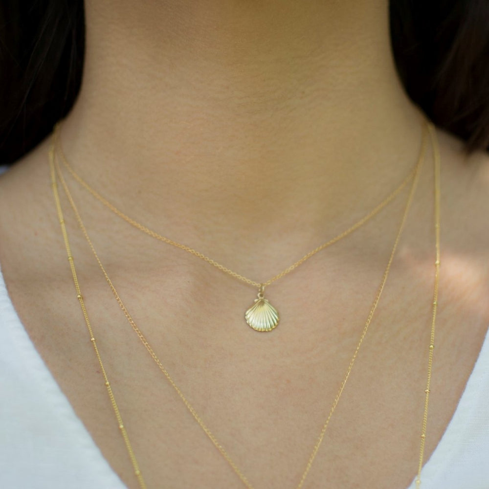 model wearing gold shell short necklace