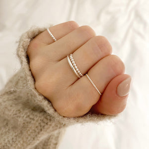 model wearing silver beaded stacking ring, twisted stacking ring, silver band and the square beaded stacking ring