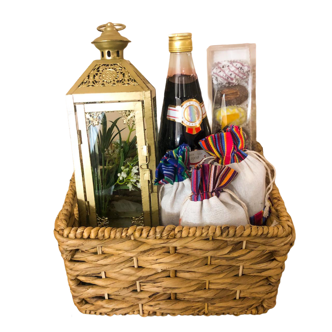 A basket containing Ramadan items, such as Vimto, chocolate covered dates, middle eastern sweets, a golden lantern from basketsat